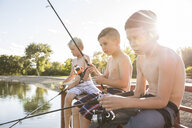 Shirtless friends fishing in lake while sitting on pier against sky during sunny day - CAVF53459