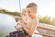 Happy shirtless friends fishing in lake while sitting on pier against sky during sunny day - CAVF53462