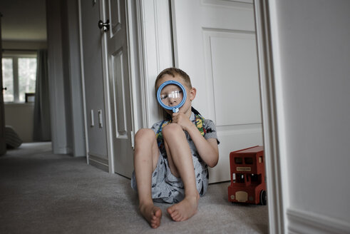 Boy looking through magnifying glass while sitting by door at home - CAVF53477