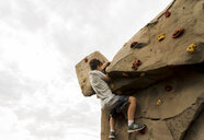 Low angle view of boy climbing boulder against cloudy sky at playground - CAVF53500