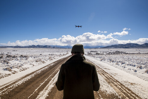 Rear view of man flying drone against sky at desert during winter - CAVF53506
