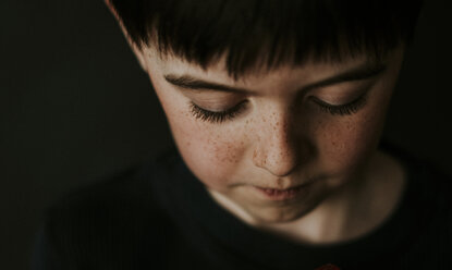 High angle close-up of boy with freckles over black background - CAVF53515