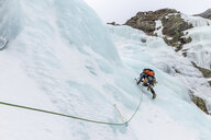 Low angle view of backpacker ice climbing at White Mountains during winter - CAVF53539