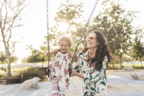 Happy mother pushing cute daughter swinging at playground - CAVF53545