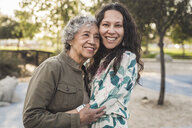 Portrait of happy daughter embracing senior mother at park - CAVF53548