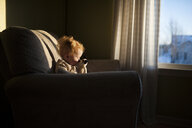 Baby boy playing with toy while sitting on couch at home during sunset - CAVF53566