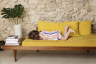 Side view of girl lying on sofa at home - CAVF53569
