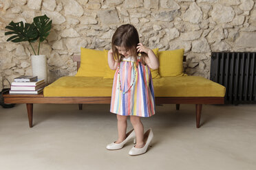Happy girl wearing big shoes while standing by sofa at home - CAVF53572