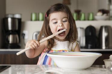 Girl tasting food on kitchen island at home - CAVF53575