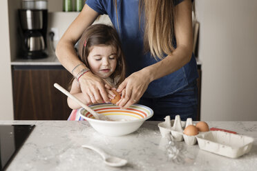 Midsection of mother assisting daughter in preparing food on kitchen island at home - CAVF53578