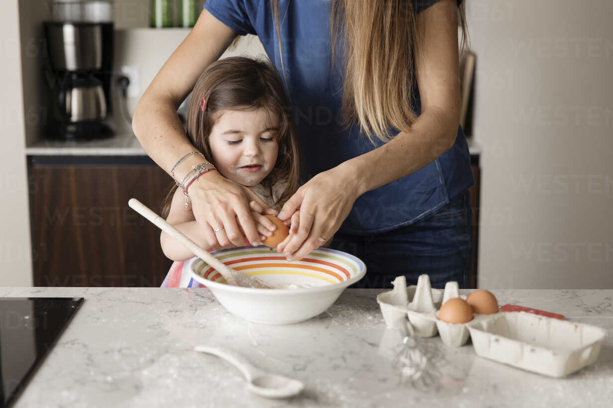 Midsection of mother assisting daughter in preparing food on kitchen island at home - CAVF53578 - Cavan Images/Westend61