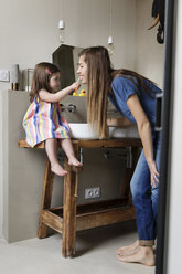 Daughter brushing mother's teeth while sitting on bathroom sink at home - CAVF53581