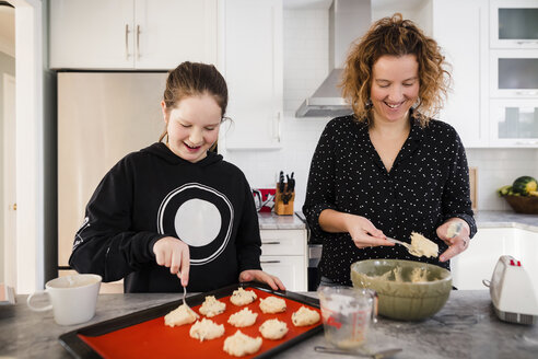 Mother with daughter putting batter on baking sheet in kitchen at home - CAVF53602