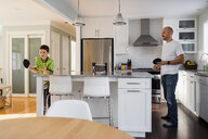 Son playing table tennis with father on kitchen island at home - CAVF53608