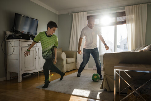 Father with son playing soccer at home - CAVF53611