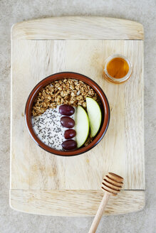 Overhead view of breakfast served in bowl on wooden cutting board at table - CAVF53617