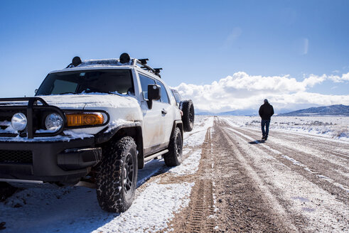 Rear view of man with off-road vehicle on dirt road amidst desert during winter - CAVF53620
