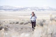 Full length of female hiker walking at desert during winter - CAVF53623