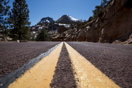 Close-up of double yellow lines on road against mountains - CAVF53629