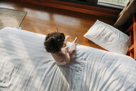 High angle view of shirtless baby girl sitting on bed at home - CAVF53647