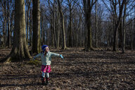 Happy girl with arms outstretched standing on field in forest - CAVF53692