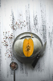 Sliced Cucurbita maxima on tin plate, kitchen knife and peppercorns - ASF06244