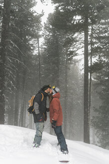 Side view of couple kissing while standing on snowy field against trees during foggy weather - CAVF53749