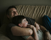 Happy father embracing son while lying on sofa at home - CAVF53770