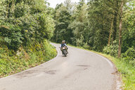 Couple riding on motorcycle in forest - CAVF53773