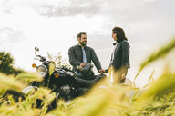 Couple talking while standing by motorcycle on grassy field against sky - CAVF53776