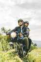Couple looking away while sitting on motorcycle against sky - CAVF53779