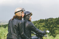 Rear view of couple looking away while sitting on motorcycle against sky - CAVF53782