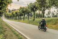 Couple riding motorcycle on road amidst trees during sunset - CAVF53785