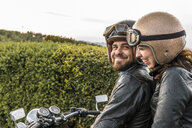 Happy couple talking while sitting on motorcycle against sky - CAVF53788