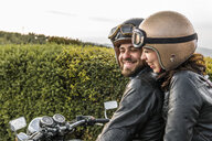 Cheerful couple talking while sitting on motorcycle against sky - CAVF53794