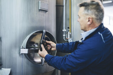 Brewer adjusting handle of storage tank at microbrewery - CAVF53815