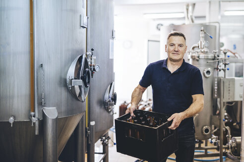 Portrait of confident brewer holding beer bottles in container while standing by storage tank at brewery - CAVF53836