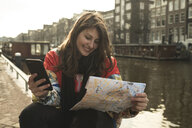 Smiling young woman holding smart phone while reading map by canal in city - CAVF53863
