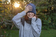 Laughing teenage girl wearing wooly hat and scarf in autumn - LBF02167