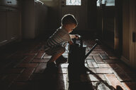 Side view of baby boy holding watering can while crouching on floor at home - CAVF53869