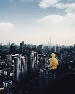 Rear view of man looking at modern cityscape against sky while standing on building terrace - CAVF53926