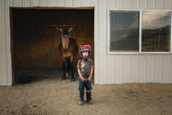 Portrait of cute boy wearing helmet while standing against horse at stable - CAVF53947