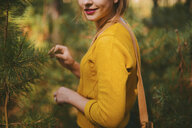 Midsection of smiling woman standing amidst pine trees at forest - CAVF53991