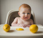 Shirtless baby boy making face while sitting on high chair with lemons in foreground - CAVF54039