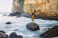 Rear view of woman standing on rock at Reunion island - CAVF54051