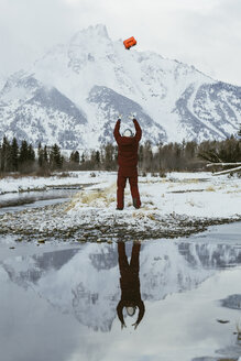 Rear view of man throwing box in air against snowcapped mountains while standing by lake - CAVF54066