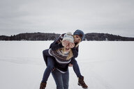 Playful woman covering friend's eyes while being piggybacked by her on snow during winter - CAVF54072