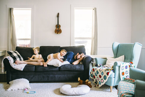 Siblings playing while father playing on sofa in living room - CAVF54087
