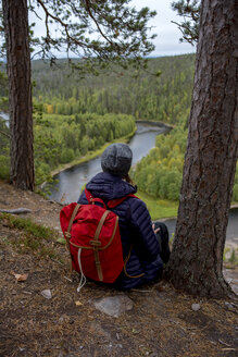 Finland, Oulanka National Park, woman with backpack sitting in pristine nature - PSIF00153