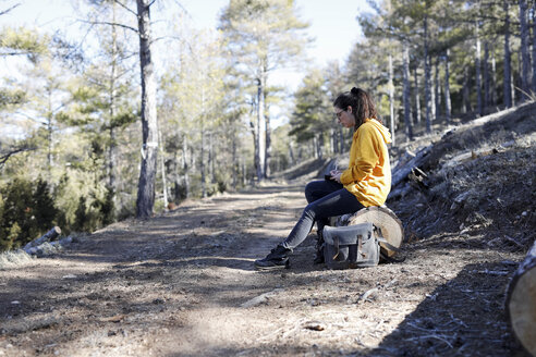 Young woman with yellow sweater in the forest, writing - GRSF00002